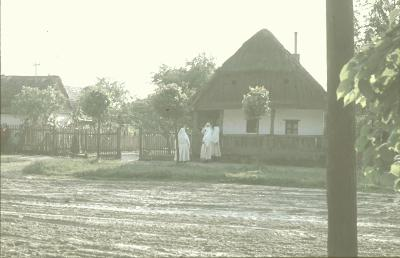Csökölyi utcarészlet fehér gyászba öltözött asszonyokkal.